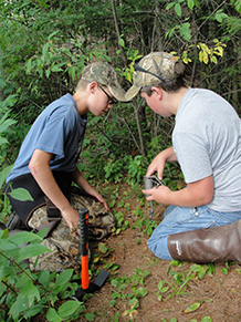 two youth set an enclosed trigger trap at Future Trappers of Wisconsin camp