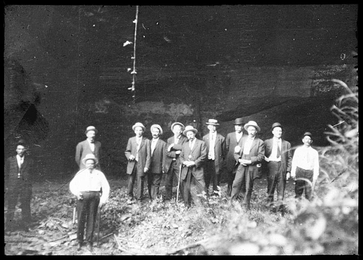 A group of men at a park party in formal suits and hats. A few carry walking sticks. One of a series of photographs most likely taken by John Nolen, the well-known landscape architect John Nolen who recommended Wyalusing become a state park.