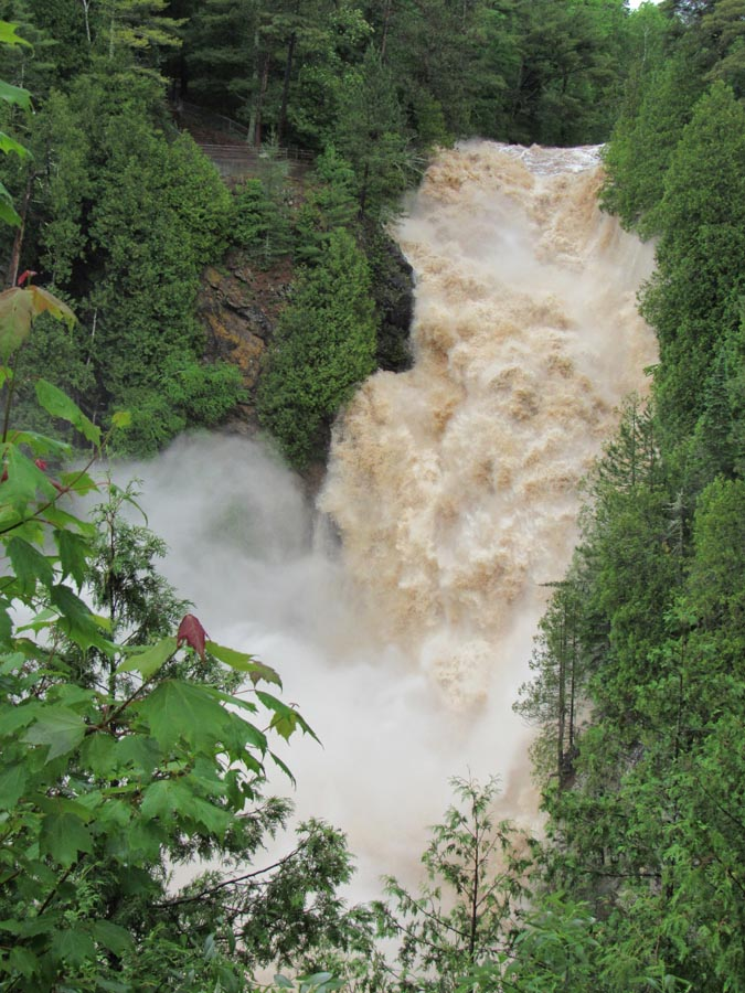 The arched bridge at Amnicon Falls State Park has so far survived the torrent of the raging Amnicon River. - Photo credit: DNR