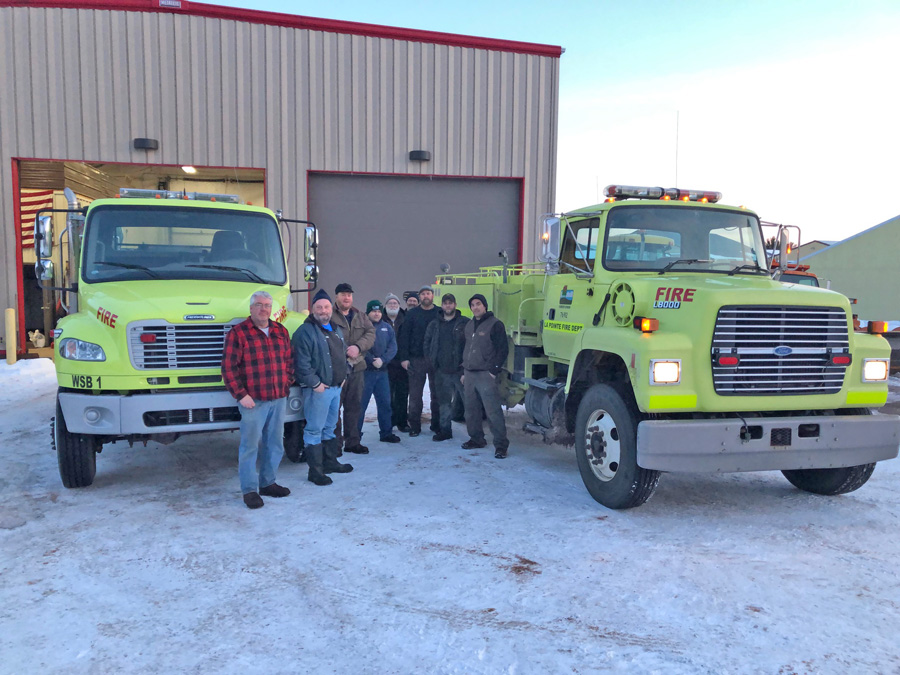 Handing off the trucks: Mark Guenter, DNR forester (left) hands over the wildland firefighting engines to members of the LaPointe Fire Department in front of the shop that will house the engines on Madeline Island. - Photo credit: DNR