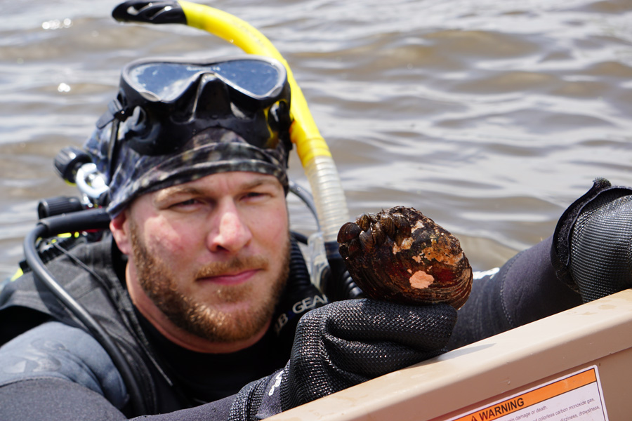 Conservation biologist Jesse Weinzinger holds a native mussel with invasive zebra mussels attached. - Photo credit: Jack Silverberg