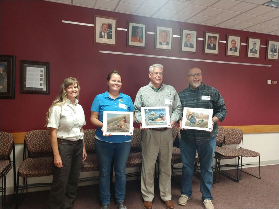 2020 stamp contest judges stand with winning artwork chosen for next year's pheasant, waterfowl and turkey stamps. - Photo credit: DNR