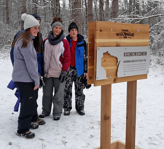 First Day Hikers take advantage of the Department of Tourism selfie photo stand to capture their hike at the Southern Unit of the Kettle Moraine State Forest. - Photo credit: DNR