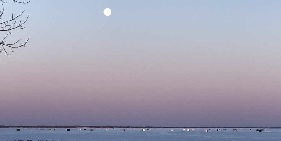 A full moon over spearing shanties on Lake Winnebago off Neenah. - Photo credit: DNR
