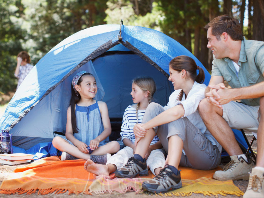 Family camping sitting on blanket outside of tent