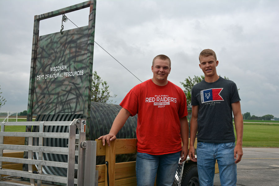 Pulaski High School students Chasten Fatla, left, a junior, and Brock Bogacz, a sophomore, built the trap in their advanced agricultural engineering class. - Photo credit: DNR