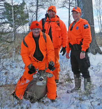 Ranger Jacob Anderson (right )with hunters he and Ranger Natalie Brown made contact with on state owned land near Superior.  Jacob helped drag the buck out for 1.25 miles for the elderly hunter.