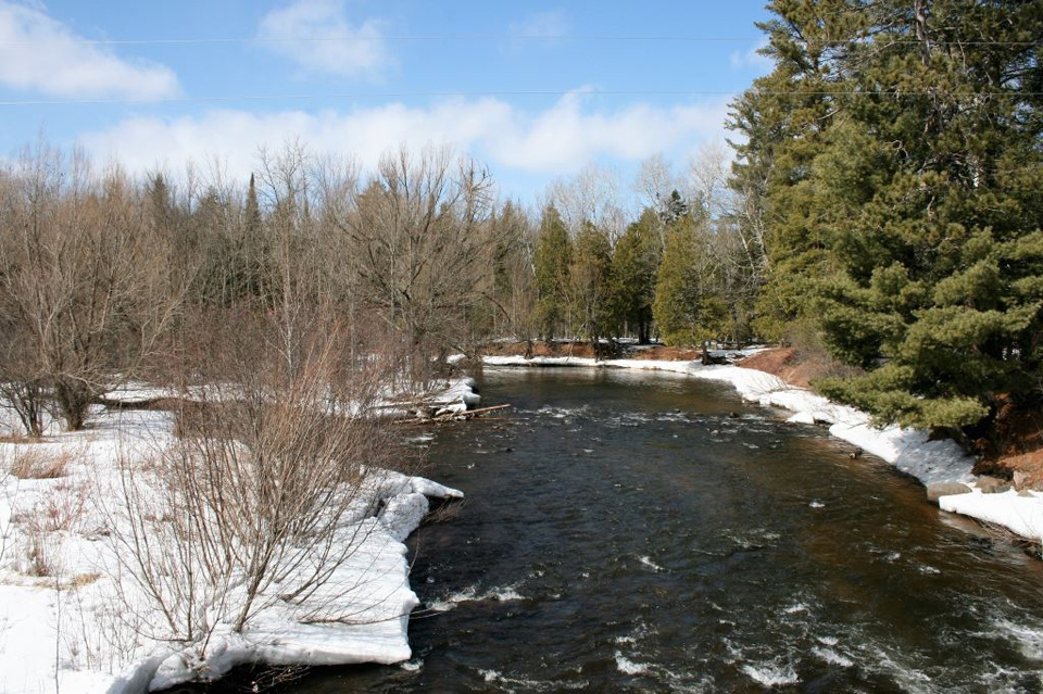 The Bois Brule River is flowing for the March 31 steelhead opener but deep snow still lines the banks. - Photo credit: DNR