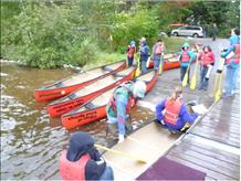 Scott Peterson with the Canoes On Wheels (COW) equipment disembarking canoes [photo]