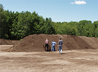 Three men stand in front of a pile of finished compost