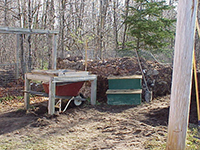 A compost bin and sifter near the edge of a yard