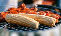 Corn and chicken cooking on an open grill