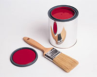 An open can of red paint, with a paintbrush