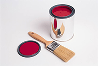 An open can of red paint with a brush