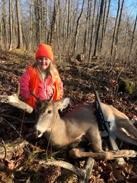 Lexi poses with her buck she shot while hunting with her dad.