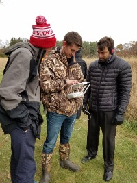 UW-Madison students Chris Bechtel, left, and Professor Chris Johnson, right, watch student Chris Bechtel operate the drone's flight.