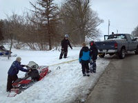 Warden Mike tows a buried snowmobile from the ditch near Brothertown.