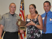 New warden Kyle E. Lynch accepts the Tyler Kreinz Tactical Proficiency Award from Mary and David Kreinz.