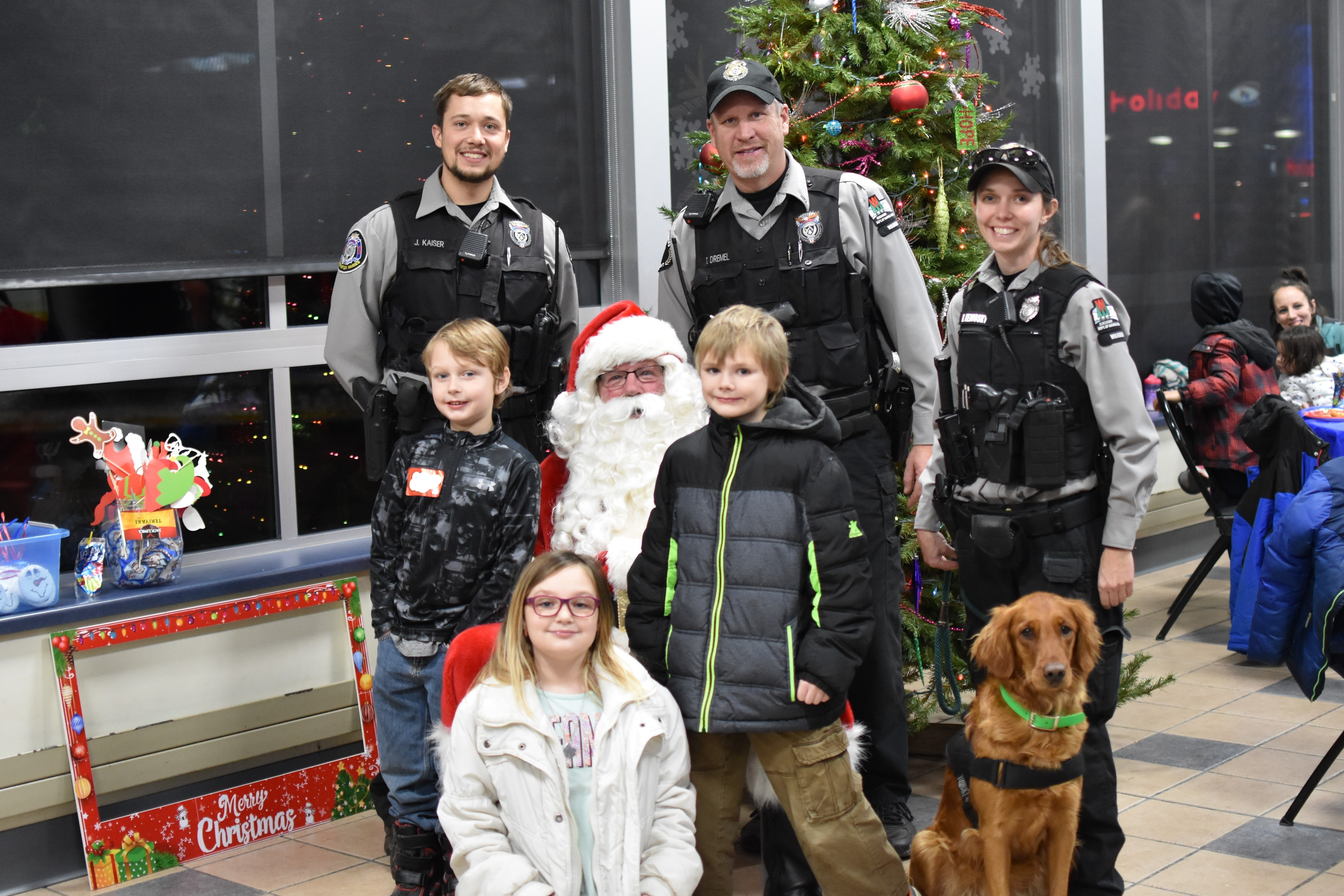 'Wardens Jonathan Kaiser, Kaitlin Kernosky and Lt. Ted Dremel and their partner shoppers at Shop with a Cop in Waupaca County.